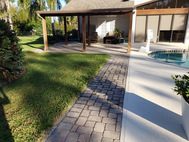 Poolside walkway made of bricks pictured without sealant in backyard of home in Tice, FL.