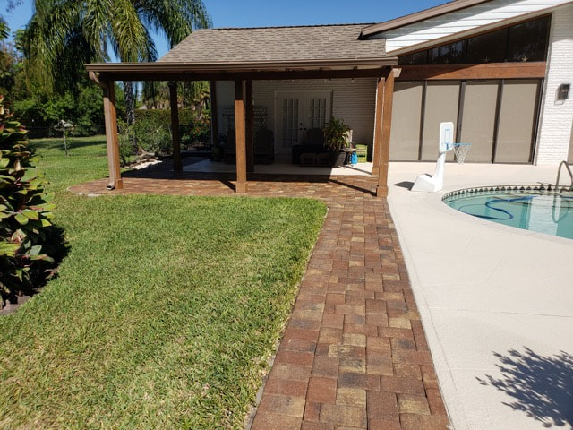 Poolside walkway made of bricks pictured with new coat of sealant in backyard of home in Tice, FL.